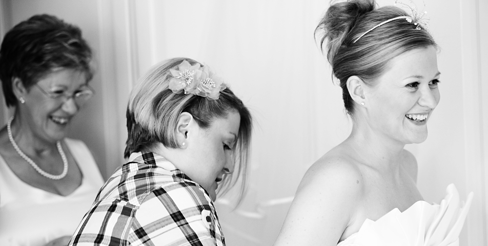 black and white wedding photography of the bride and mother putting on the wedding dress