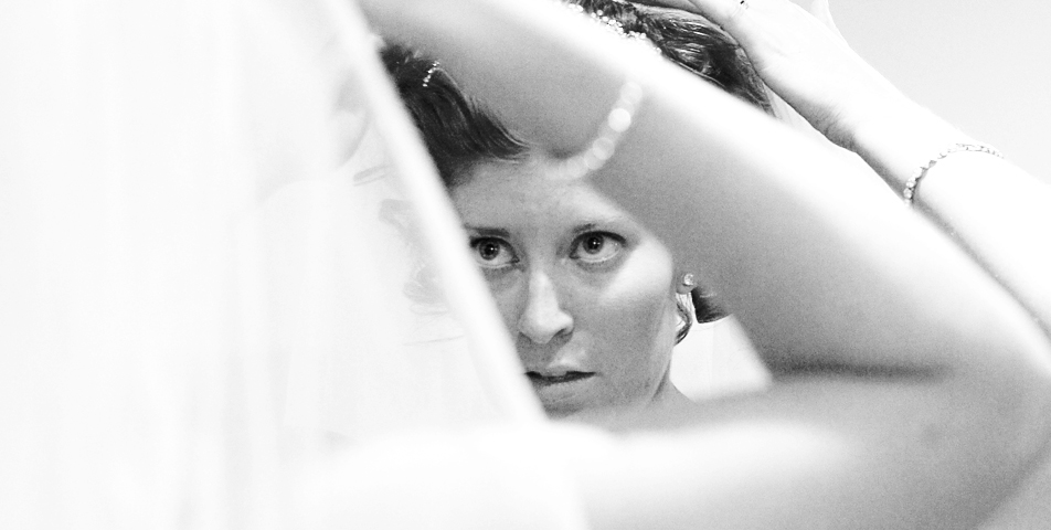 photography of the bride putting the finishing touches to her wedding viel and tiara
