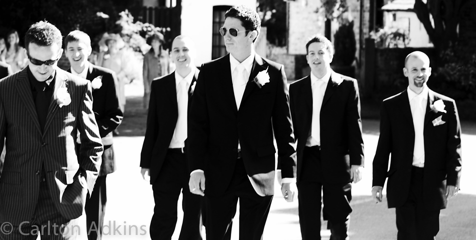 photography of the groom and ushers walk to the church for the wedding ceremony in cheshire
