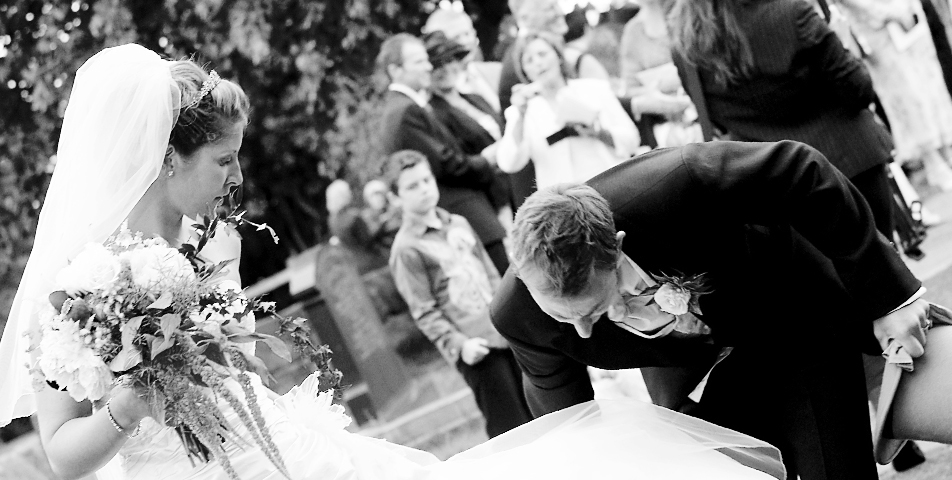 photography of the groom helping the bride with her beautiful designer wedding dress in wilmslow Cheshire