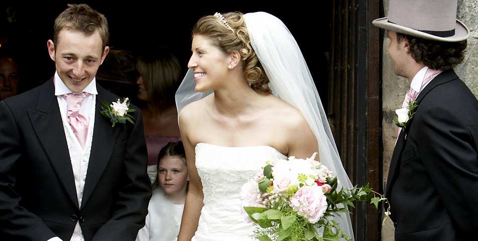 the bride come out of st Bartholomews church after the wedding ceremony in Cheshire