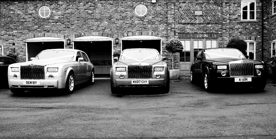 the classic rolls royce wedding cars lined up and ready to take them to the church on time