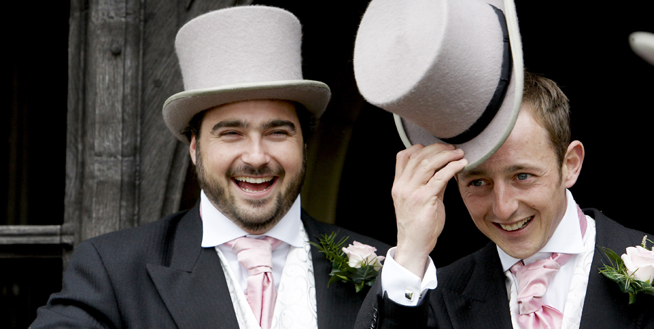 wedding photography of the groom and bestman in their top hat and tails outside the church in Wilmslow