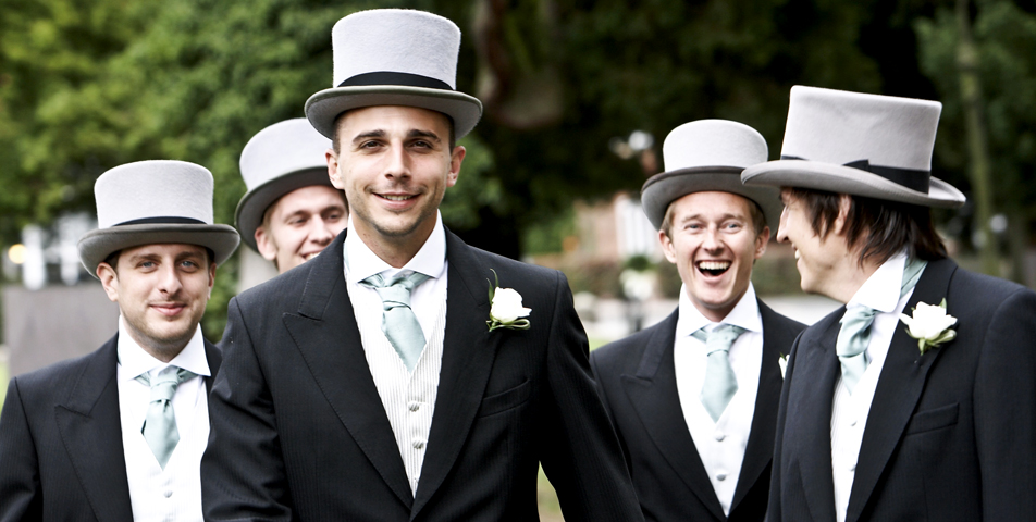 The groom and best man in traditional top hat and tails arrive at the church on time