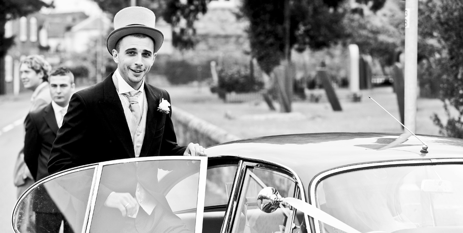 The groom getting into the classic wedding car