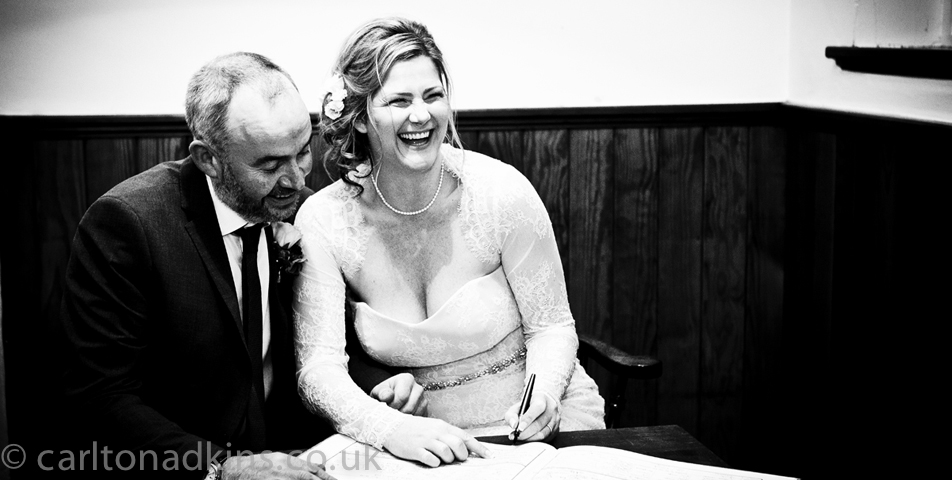 photography of the bride and groom signing the marriage certificate